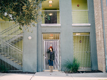 A young woman stands in front of a door at an apartment complex.