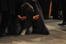 Woman kneeling with arms extended, praising God during worship service.