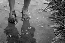 The feet of a child walking in mud