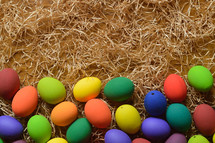 Colorfully painted Easter egg border on straw.