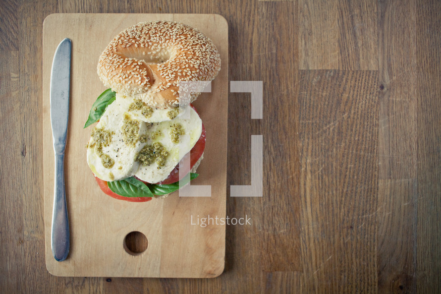 eggs, tomato, and basil on a bagel