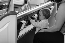 toddler boy playing with hymnals in the back of a pew in a church