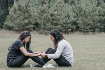 friends holding hands in prayer