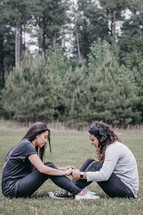 two women sitting in grass holding hands and praying
