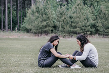 young women holding hands in prayer