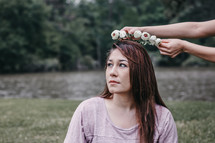placing a crown of flowers on a woman's head