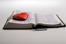 red stone shaped heart stone on pages of a Bible