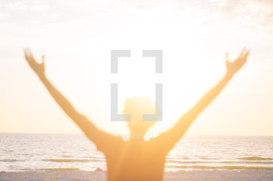 blurry image of a man with raised hands standing on a beach