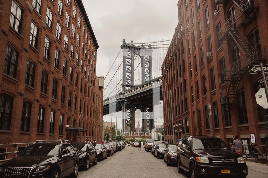 Brooklyn bridge and cars parked on a narrow street