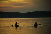 paddling kayaks at sunset