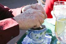 an elderly man putting sugar in tea
