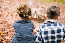 children sitting outdoors with their backs to the camera on a fall day