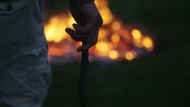 Young Man Throws Stick into a Bonfire