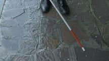 blind man walking on a sidewalk