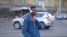a young man listening to headphones and dancing on a street