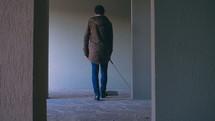 blind man walking in a hallway