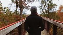 a woman walking on a wood deck looking at fall colors