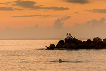 man swimming in the ocean at sunset