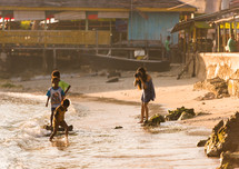 a woman photographing kids playing in the sea waves in Luwuk