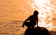 child standing on a rock at sunset along a shore
