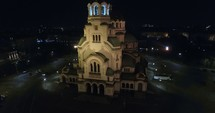 aerial view over a city church and bell tower at night
