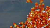 candy corn dropping into a bowl