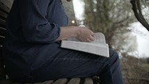 a person sitting on a bench reading a Bible