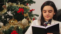 Girl reading a book while sitting near Christmas Tree Close up