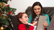 sisters talking on a tablet near a Christmas tree