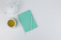 tea pot, cup, saucer, journal, pencil on a white table