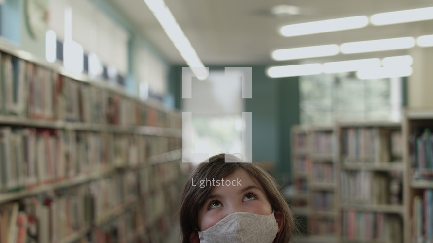 girl at a library wearing a face mask
