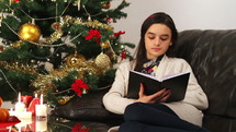 Girl reading a book while sitting near Christmas Tree at home