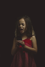 little girl singing into cellphone with feeling