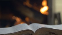 open Bible in front of a fire
