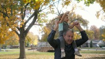grandfather with his granddaughter playing in fall leaves