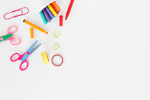 scissors, markers, and paperclips on a white background