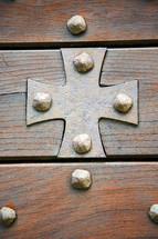 brass cross and a wood door