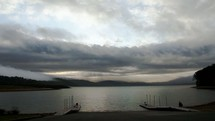 Cloud movement over a lake near a boat dock.