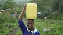 girl walking balancing a jug of water on her head