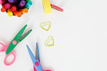 scissors, markers, and paper clips on a white background