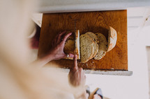 a woman slicing bread in a kitchen