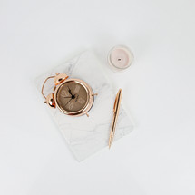 rose gold, alarm clock, flower, notebook, pen, and candle on white desk
