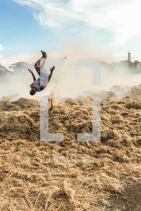 man doing a flip in a burning field in Haiti
