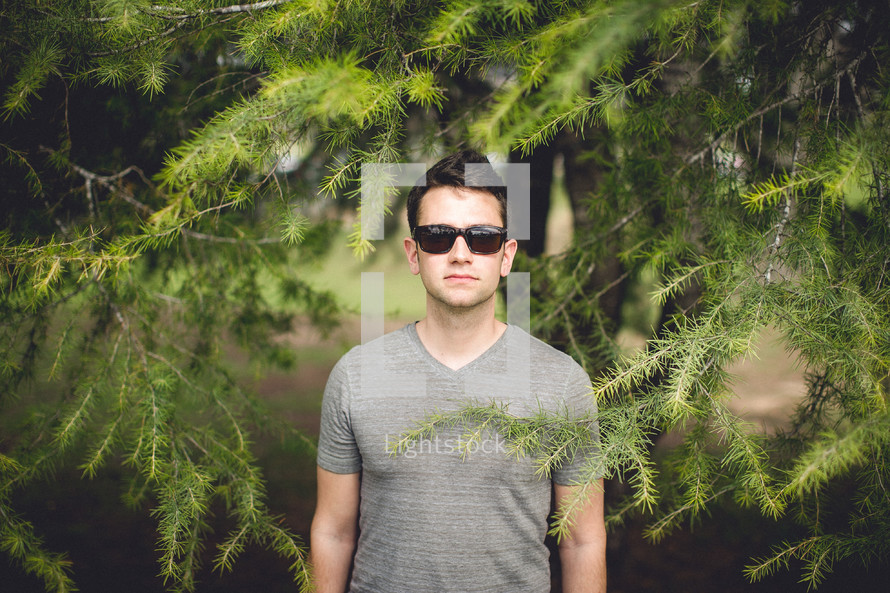 man in sunglasses standing under a tree