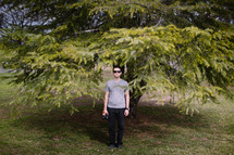 man standing in front of a tree