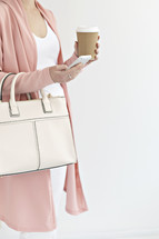 a woman with a purse holding a coffee cup