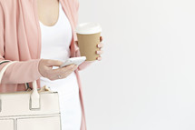 a woman with a purse holding a coffee cup and texting on a cellphone