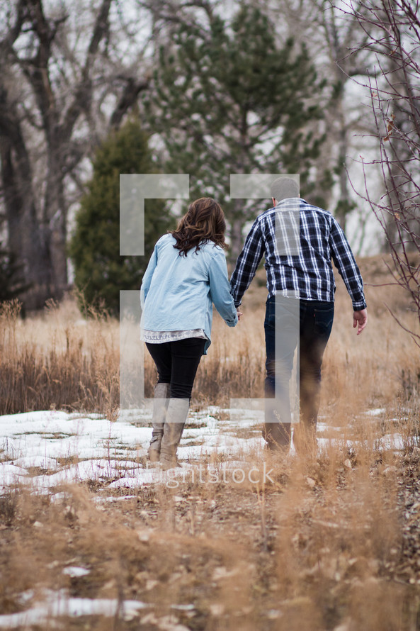 a couple walking holding hands through a snowy field