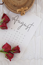 red roses on an August calendar