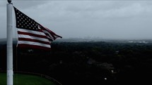 American flag on a flagpole overlooking a city